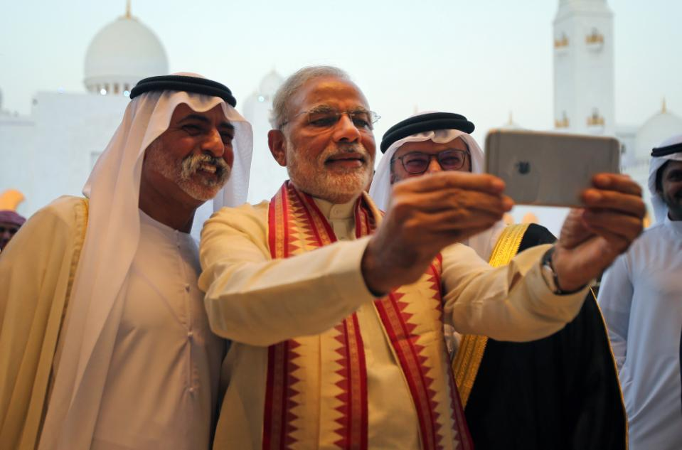 Indian Prime Minister Narendra Modi, middle, takes a selfie next to Sheikh Hamdan bin Mubarak Al Nahyan, UAE Minister of Higher Education and Scientific Research, left, as they tour the Sheikh Zayed Grand Mosque during the first day of his two-day visit to the UAE, in Abu Dhabi, United Arab Emirates, Sunday, Aug. 16, 2015.  The UAE is home to over two million Indian expatriates and this is the first visit by an Indian premier in over three decades. (AP Photo/Kamran Jebreili)